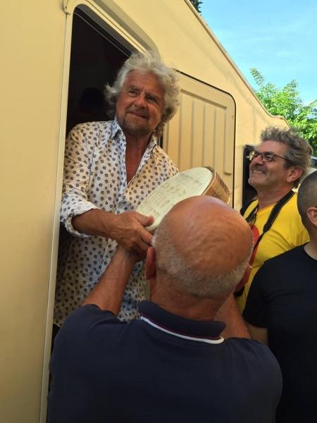 Il momento della consegna del formaggio a Beppe Grillo da parte di Columbu (Foto Tiziana Ciprini)
